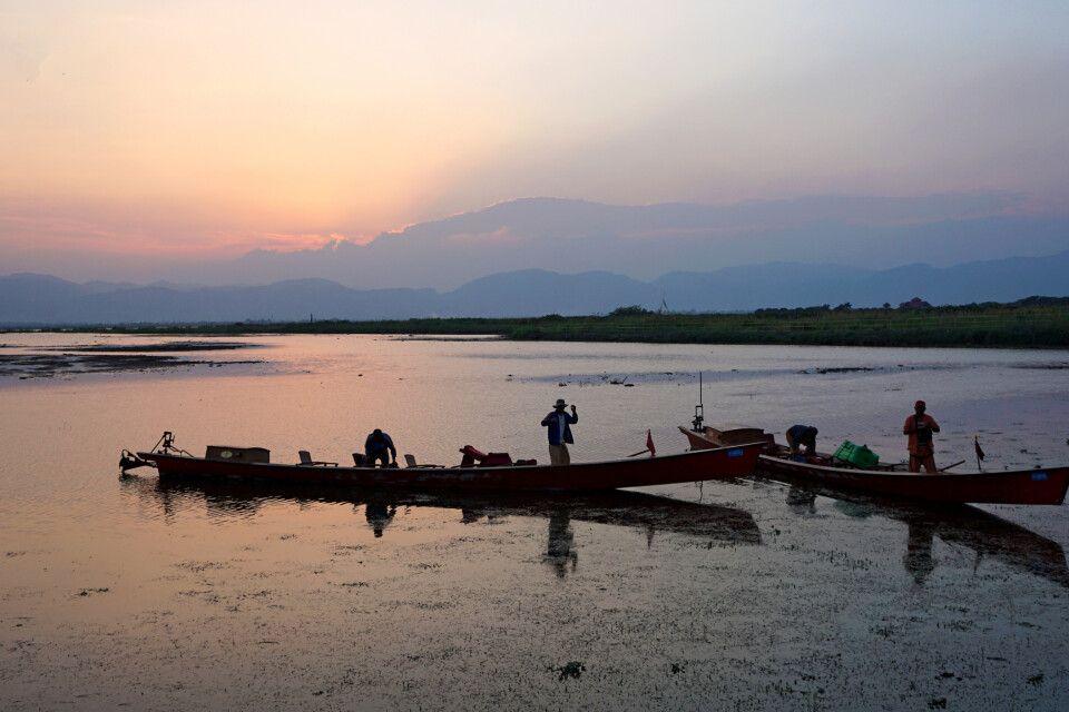 Silhouetten der Boote im Sonnenuntergang am Inle-See