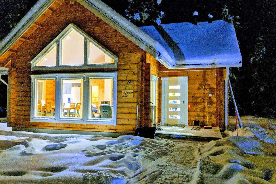 Gemütliche Blockhütte bei Nacht