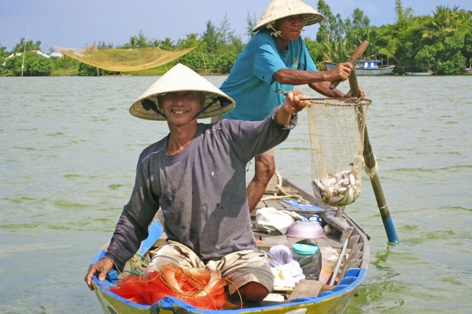 Fröhliche Fischer mit ihrem Fang in Hoi An
