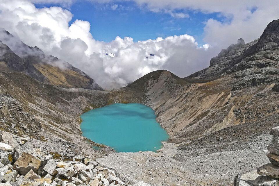 Viele Steinmännchen säumen die blaue Berglagune