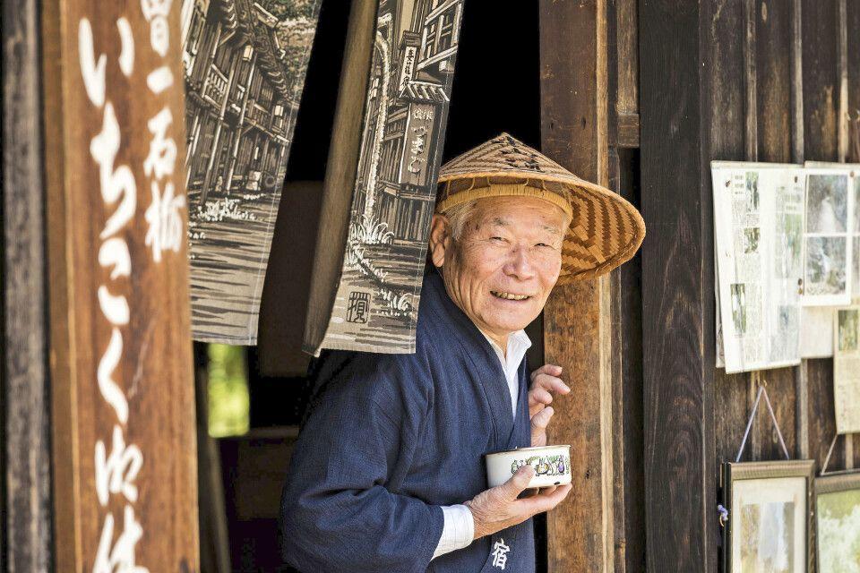 Ein freundlicher Japaner serviert in einem traditionellen Teehaus Tee für die vorbeikommenden Wanderer entlang des Nakasendo in Kiso.